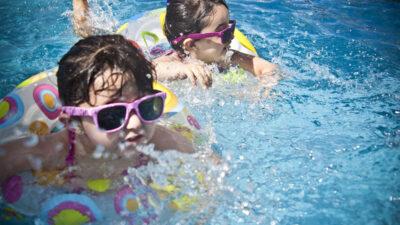 Två barn som badar med badringar och solglasögon.