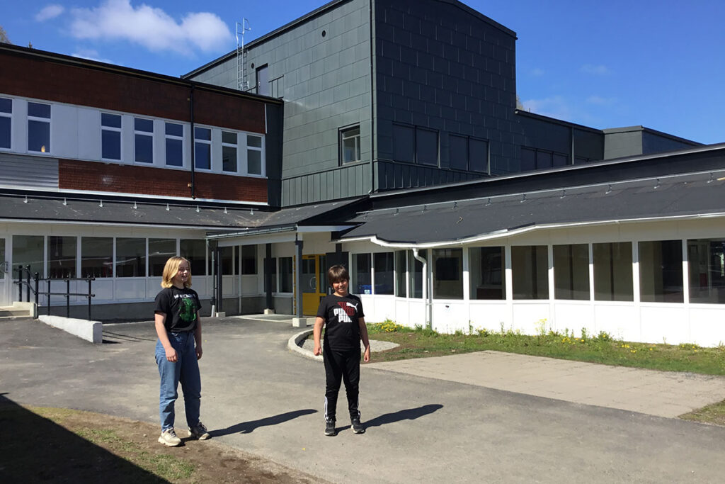 Två elever som står framför Pitholmsskolans nya tillbyggnad.