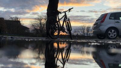 En vattenpöl i förgrunden och sedan en cyklist samt en solnedgång.
