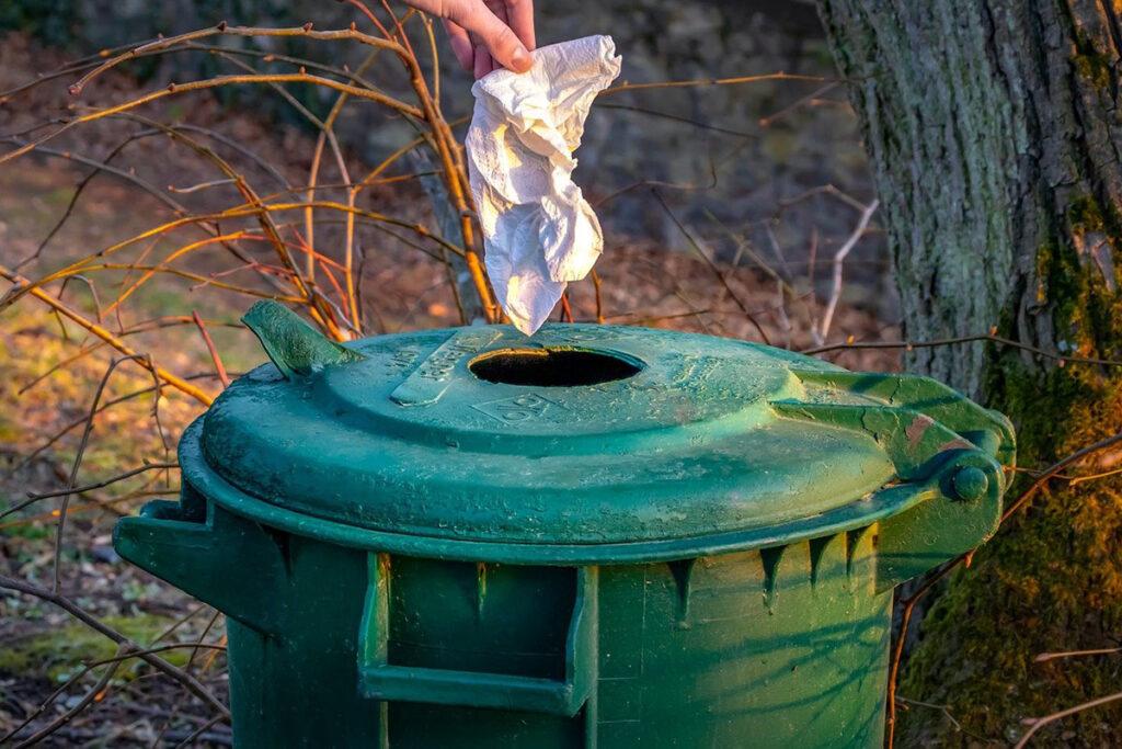 Någon slänger ett papper i en grön soptunna.