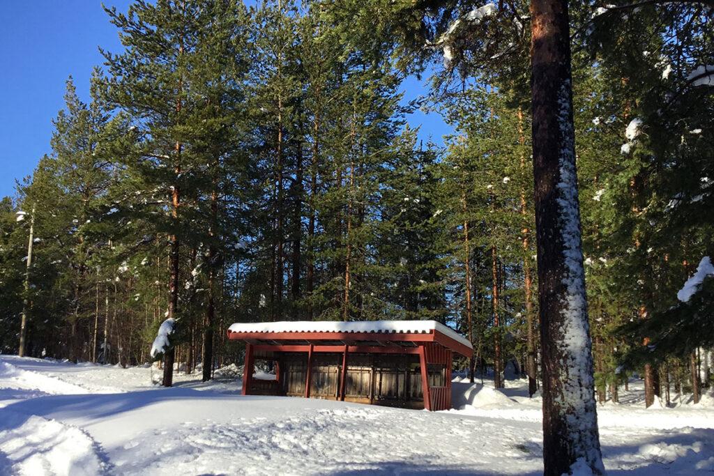 Ett rött vindskydd, granskog och snö.