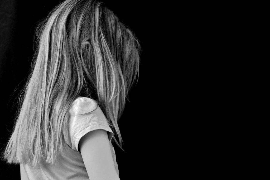 Ett barn som står lite bortvänt. Barnet är omgivet av mörker.