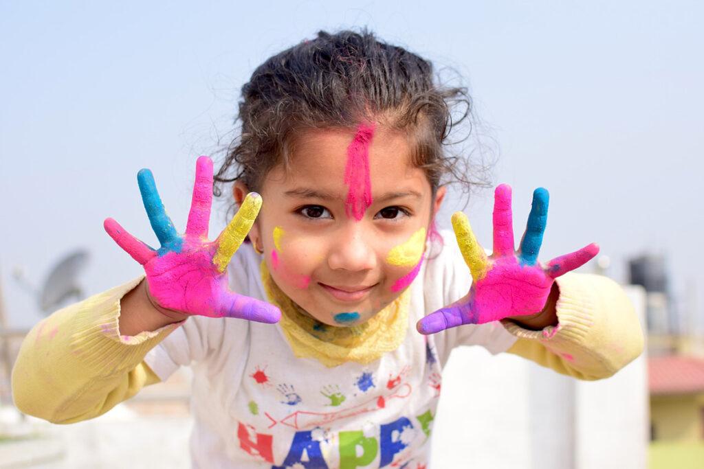 Flicka med målarfärg i ansiktet och på händerna