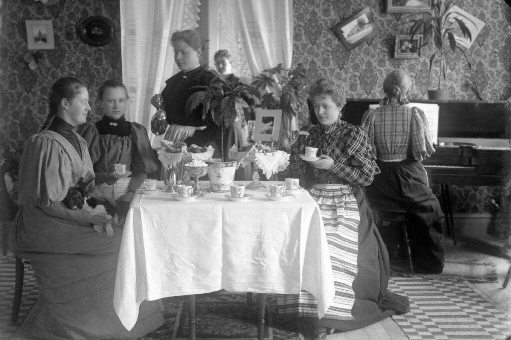 Damer som fikar. De sitter vid ett bord med vit duk på.