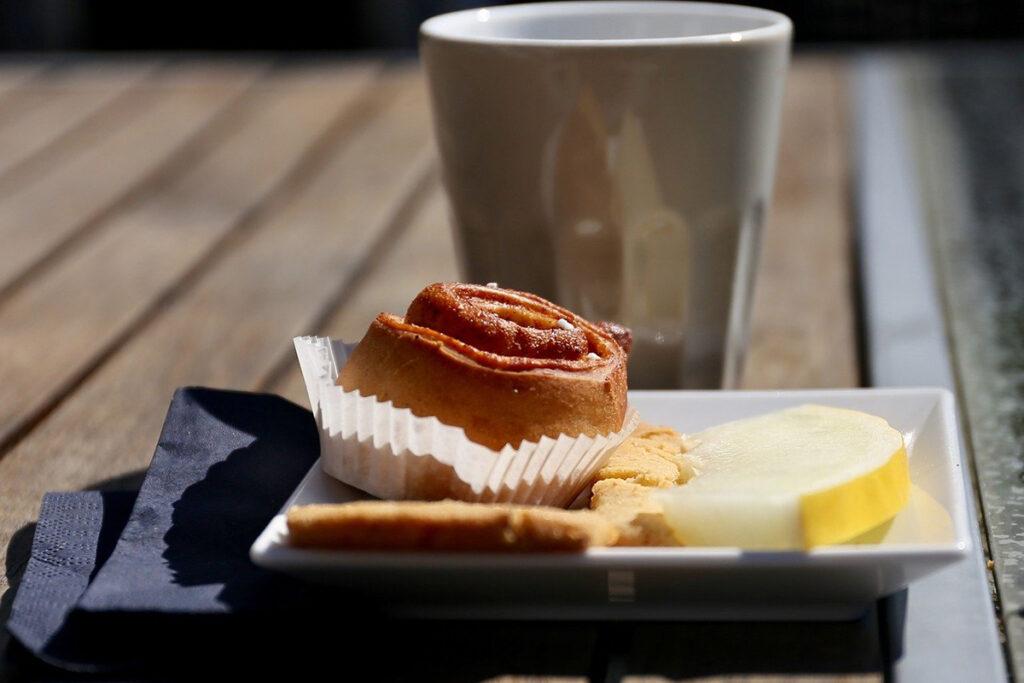 Kanelbulle, melon och en kaffekopp på en brygga.