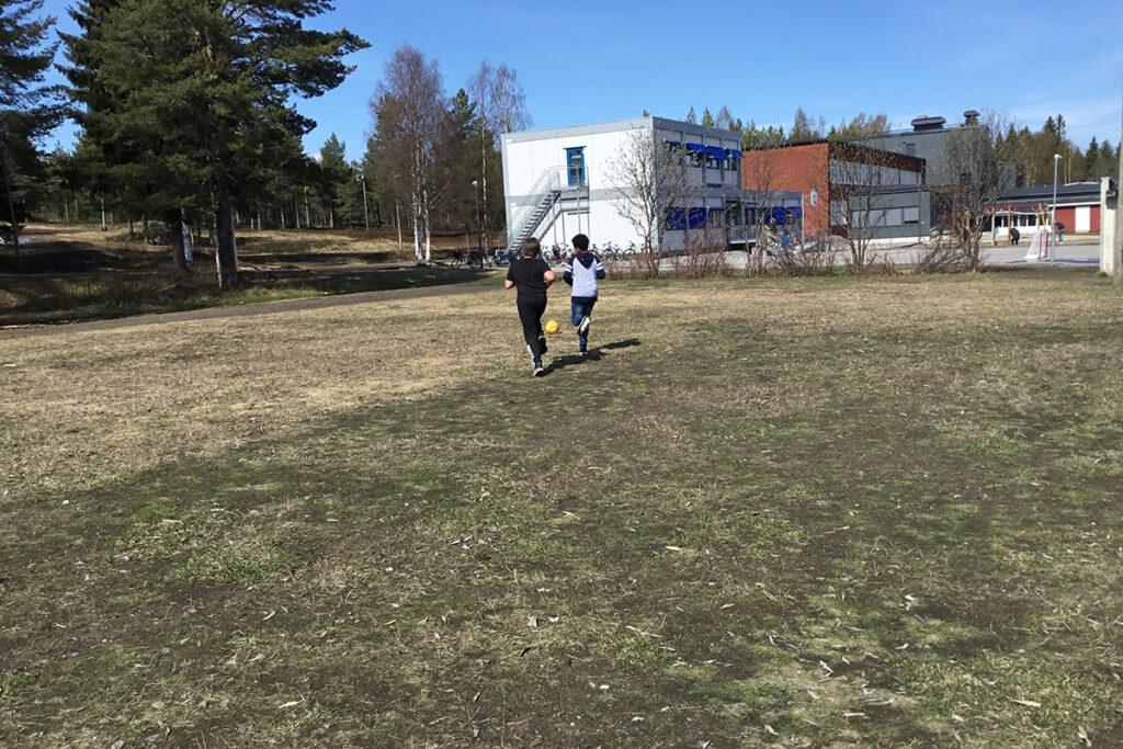 Två elever som springer på fotbollsplanen.