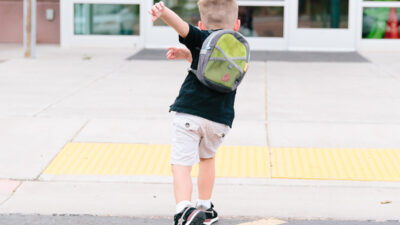 Ett skolbarn som springer in i skolan.