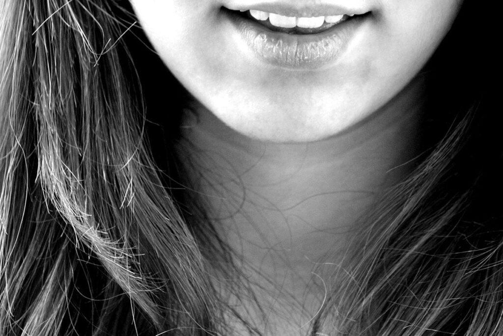 En svartvit närbild på en person som ler.