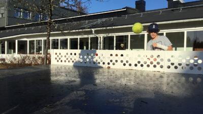 En tennisboll som flyger över nätet på ett pingisbord.