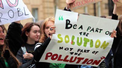 """En tjej protesterar mot klimatförändringarna. Hon håller i ett plakat med texten """"Be a part of the solution, not a part of the pollution""""."""